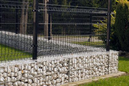 Un cimiento bajo debajo de una valla de acero calado. Tejado.
