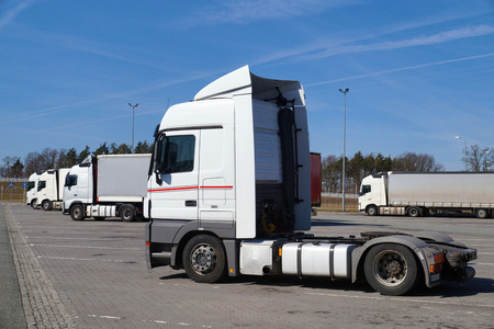 Geparkeerde vrachtwagens. Op de voorgrond een trekker zonder oplegger.