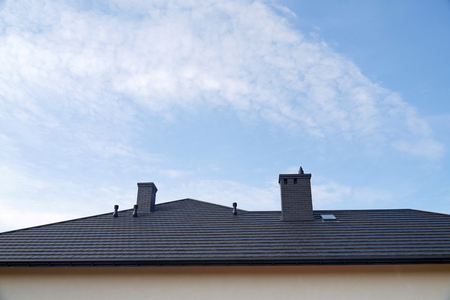 A newly built residential house. A fragment of the roof made of metal roof tiles. Reklamní fotografie