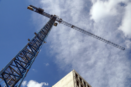 Frame shot from the construction site, view from below on the building being built and a construction crane.