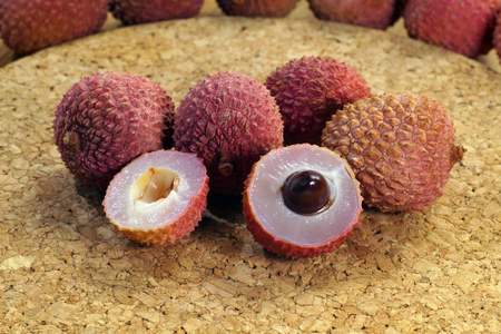 For dessert. A view of the cross-section of a lychee fruit with seed, next to whole fruits.