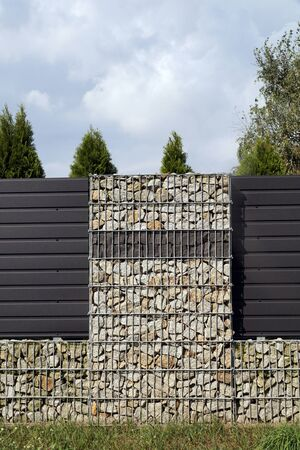 An unusual and and attractive type of house fencing. Stone wall-gabions.