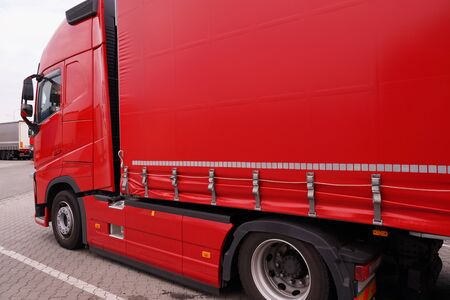 Truck with semi-trailer with covered tarpaulin. Transport and unloading. Reklamní fotografie