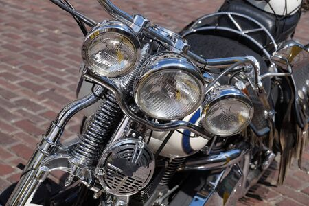 A motorcycle full of chrome elements, chopper type. Front view of a motorcycle lamp.