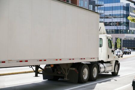 A city on the east coast of the USA. A large truck with a semitrailer in city traffic. Stock fotó