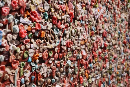 Gum wall. Chewing gums stuck to the wall. One of the tourist attractions  in Post Alley in Downtown Seattle.