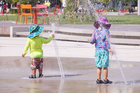 Hot summer. Colorful children dressed in streams of water from the fountain.