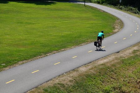 Park on the Sammamish River in Redmont. Cyclist riding on a bicycle path.
