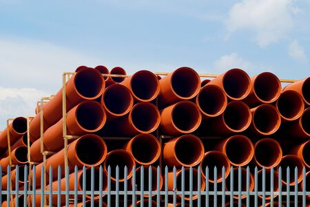 Composition of building materials. Sewer pipes stacked on shelves.