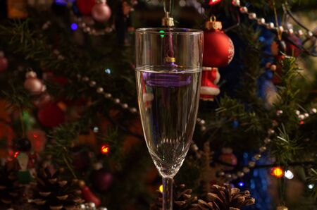 New Year. A glass of New Years champagne on the background of Christmas decorations.