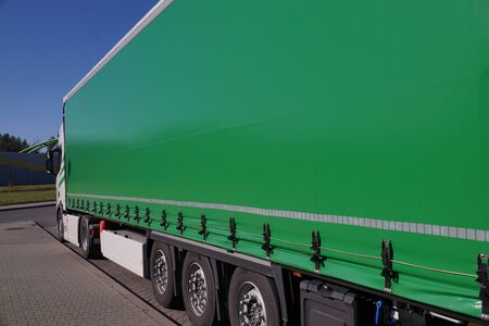 Truck transport. View of the green tarpaulin covering the semi-trailer of the truck.