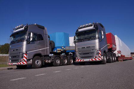 Dos camiones con semirremolques especiales para el transporte de cargas de gran tamaño. Carga de gran tamaño o convoy excepcional. Foto de archivo