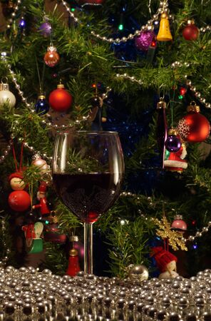 A glass of red wine on the background of the Christmas tree. In a festive mood. Stock Photo