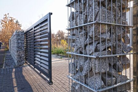 Automatic entrance gate used in combination with a wall made of gabion. Stock Photo