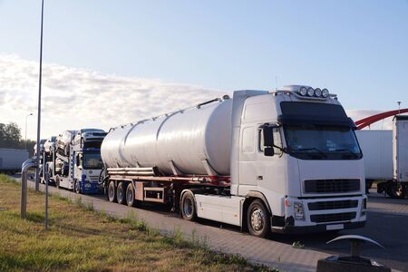Trucks transporting various goods. Photo shows a tanker and a truck for transporting passenger cars. Road transport.