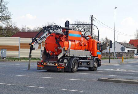 El automóvil se mueve al siguiente pozo de alcantarillado. Camión especialista. Foto de archivo