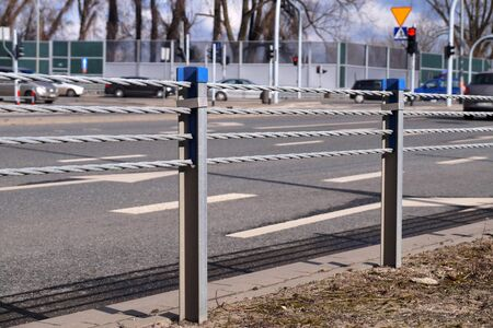 Cable barrier, also called guard cable or wire road safety barrier, is increasingly used road safety. Close-up view of posts and ropes.