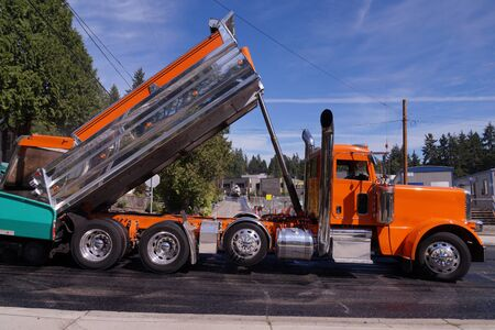 The tipper delivers another portion of asphalt. Roadworks. Laying a new asphalt layer on the road surface.
