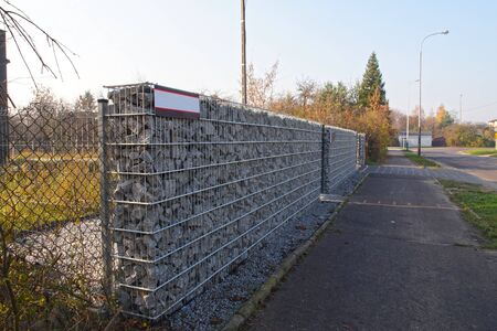 Wall separating the house from the street made of gabions. Autumn.