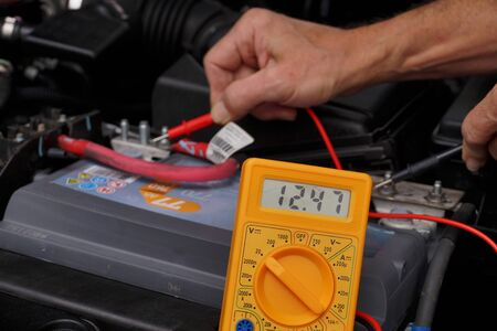 Battery voltage measurement with a meter. Car repair shop.  Stock Photo