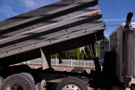 A large vehicle in city traffic. Truck with dump trailer.  Stock Photo