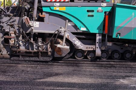 Road construction. Heavy asphalt laying machine during work.  Stock Photo