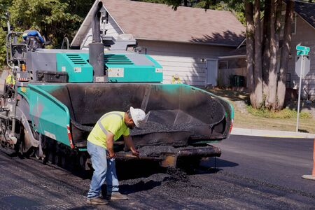 The worker uses a shovel to spread hot asphalt on the road of the bitumen laying machine. Road construction.