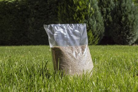 Sowing grass, setting up a lawn. Foil packaging with grass seeds.  Stock Photo