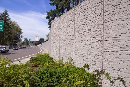 Protection of residents against noise generated by car traffic. Concrete acoustic barriers decorated with a structural pattern of stones.
