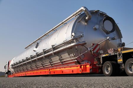 A truck with a special semi-trailer for transporting oversized loads. Oversize load or exceptional convoy.  스톡 콘텐츠