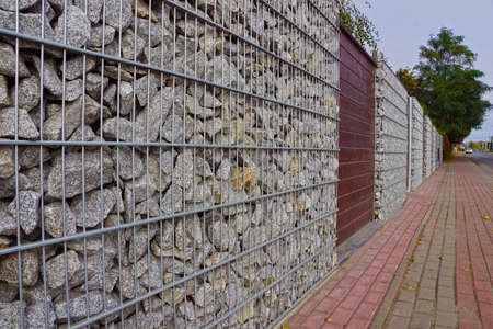 Gabions. A fragment of a fence made of gabions. Separation of the street from residential areas. Фото со стока