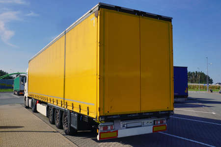 Truck transport. View of the yellow tarpaulin covering the semi-trailer of the truck.