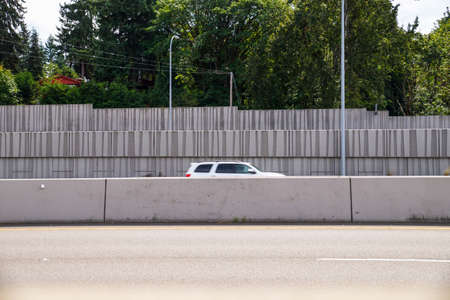 Protection of residents against noise generated by car traffic and separation of lanes. Concrete acoustic barriers decorated with a structural pattern.