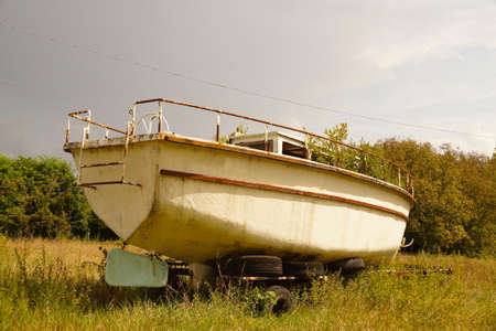 Lonely, forgotten, old abandoned boat. The deck is covered with vegetation.