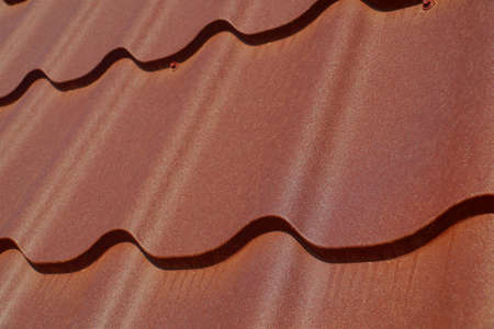 A frequently used method of covering the roof. A fragment of a roof made of steel tiles.