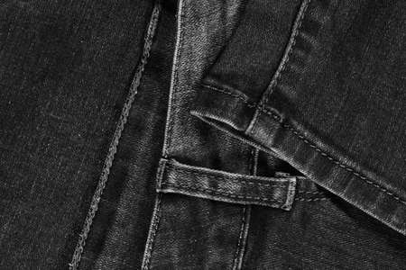 Black jeans fabric (denim). View of the waistband and leg stitches.