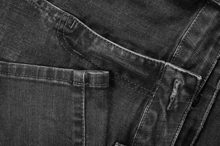 Black jeans fabric (denim). View of the seams of the legs and front of the pants.