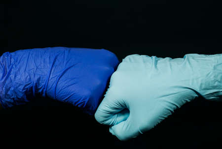 A symbolic form of greeting-hello in the time of the pandemic. The two person bumping fists together (in protective gloves) on black background.