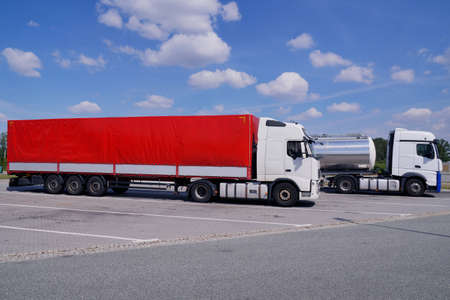 Trucks during a stopover. In the foreground a truck with a red tarpaulin in the background, a cistern. Truck stop on the highway. Standard-Bild