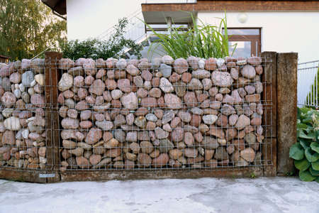 A specific form of a gabion made of pebble stones. Self-made fence made of stones.