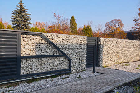 Automatic entrance gate and wicket integrated into the wall made of a gabion. A fence made of gabions. Standard-Bild