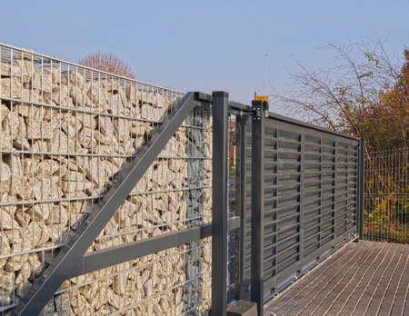 Automatic entrance gate used in combination with a wall made of gabion. Standard-Bild