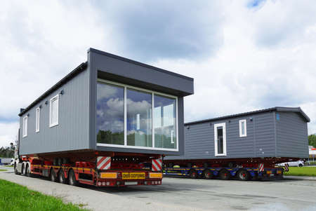 A very long and wide vehicle. Oversized cargo or exceptional convoy. A truck with a special semi-trailer for the transport of oversized cargo - transport of finished houses.