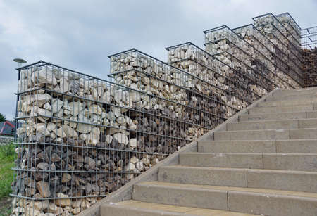 Interesting arrangement of the park space with the use of gabions. Steel baskets filled with two colors of stones.
