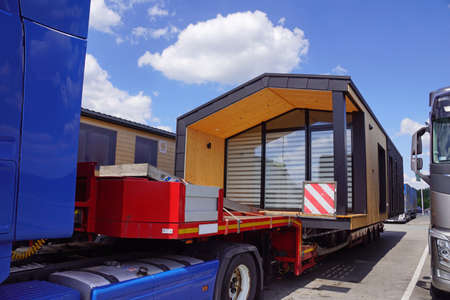 Oversized cargo or exceptional convoy (convoi exceptionnel). A truck with a special semi-trailer for the transport of oversized cargo - transport of finished houses. Banque d'images