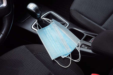 A symbolic picture of life during a pandemic. Protective hoods suspended from the gear lever in the car. Banque d'images