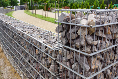 A long wall made of gabions separating the busy street from the park area. Garden architecture.