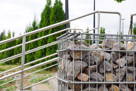 Gabions as architectural elements in combination with stainless steel. Garden architecture.