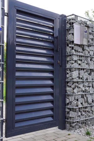 Entrance door with access control system and intercom. Gabion wall.