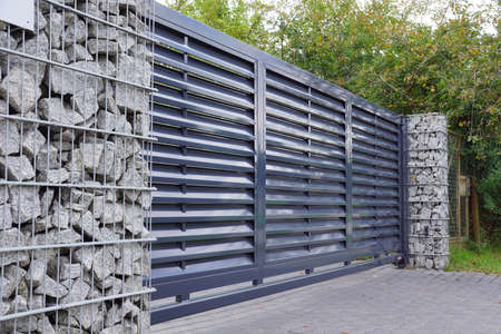 Automatic entrance gate used in combination with a wall made of gabion. Banque d'images